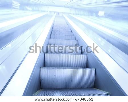 high-speed moving escalator inside airport - stock photo