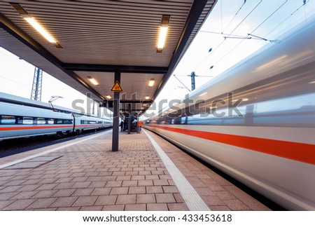 High speed  passenger train on railroad track in motion at sunset. Blurred commuter train. Railway station in Nuremberg, Germany. Industrial landscape