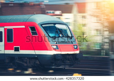 High speed passenger train on tracks in motion at sunset. Commuter train. Railway station in Nuremberg, Germany. Railroad with vintage toning