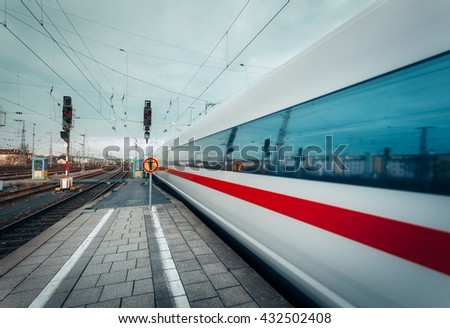 High speed passenger train on tracks in motion. Blurred commuter train. Railway station in Nuremberg, Germany. Railroad with instagram toning - stock photo