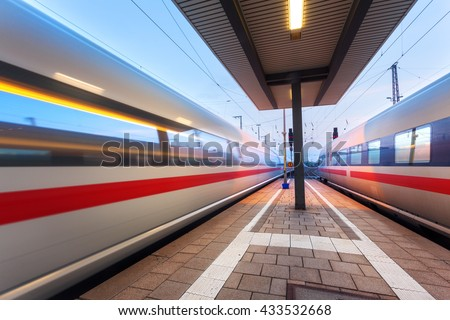 High speed passenger trains on railroad platform in motion at dusk. Blurred commuter train. Railway station in Nuremberg, Germany. Industrial landscape - stock photo