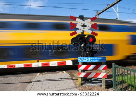 High speed train passing a railway crossing - stock photo