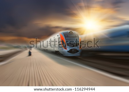High-speed train passing station with motion blur, majestic clouds and sun on background - stock photo