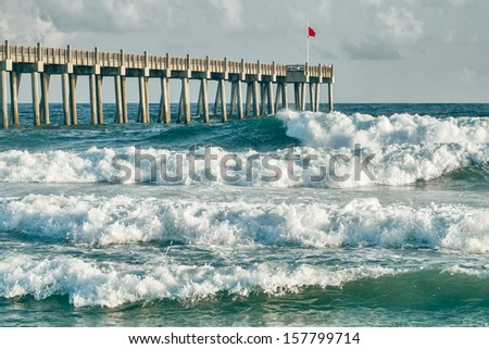 HIgh surf day preceding tropical storm. View of pier and ocean waves in Pensacola, Florida. - stock photo