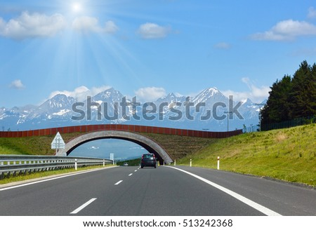 High Tatras spring sunshiny view with snow on mountainside and highway (Slovakia)