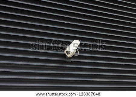 High tech overhead security camera on the metal wall - stock photo