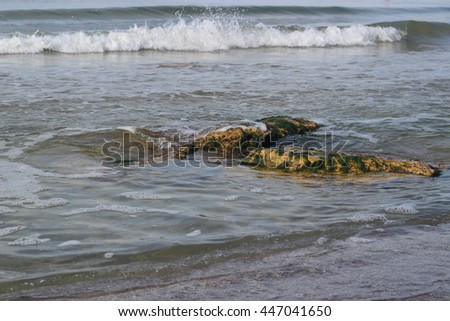 High tide wave and sand beach and stones in the surf - stock photo