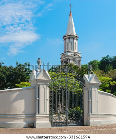High tower turret steeple of the church under blue sky with vintage gate on front - stock photo