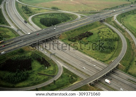 High view from plane on green scenery with beautiful round crossroads and bridges with cars driving on road onnatural background, horizontal picture - stock photo