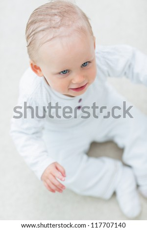 High view of a baby sitting on the floor in living room - stock photo