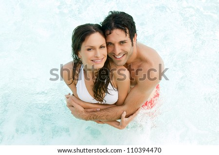 High view of a smiling couple embracing together in the water at summer