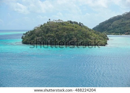 High view of a tropical island with lush vegetation in the lagoon of Huahine, motu Vaiorea, Bourayne bay, Pacific ocean, French Polynesia
