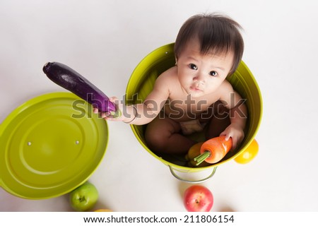 high view of adorable Asian child looking up. Isolated on white. Cute baby play with fruits - stock photo
