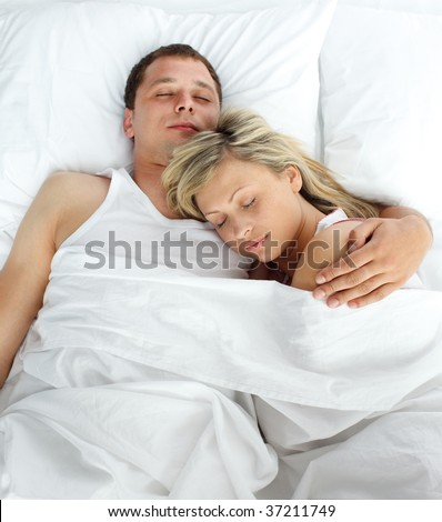 High view of couple sleeping in bed together - stock photo