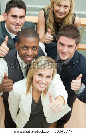 High view of happy business team with thumbs up and smiling at the camera - stock photo