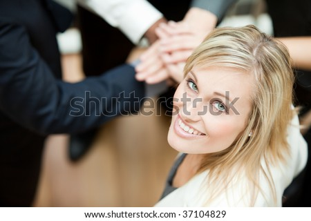 High view of people with hands together with a businesswoman smiling at the camera. Concept of union in business