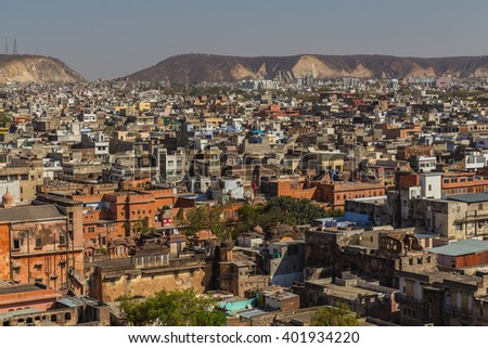 High view over the city of Jaipur in India showing lots of buildings and hills in the distant. - stock photo