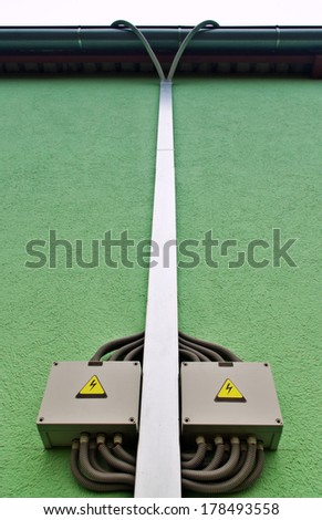 High voltage boxes with cables by the cable or wire tray on the green wall - stock photo