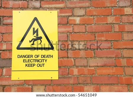 high voltage danger yellow sign on a brick wall building - stock photo