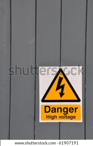 high voltage danger yellow sign on a wooden plank background - stock photo