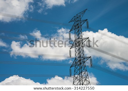 High voltage electric post against blue sky white clouds