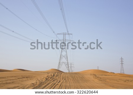 High voltage electric power transmission lines with pylons as part of power grid in red sand desert landscape scene with sand dunes in United Arab Emirates, Arabia, with blue sky - stock photo