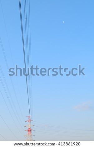 high voltage electric tower and moon