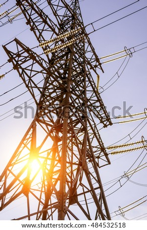 High voltage electric tower line at sunset the sun.