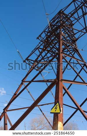 High voltage electric tower with sign against blue sky - stock photo