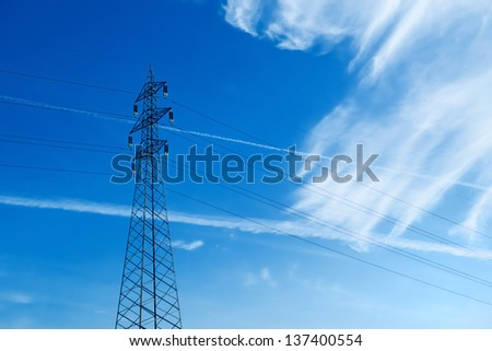 High voltage electric transmission cables over a blue sky