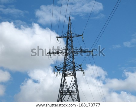 High voltage electrical power transmission line tower on blue sky with white clouds background