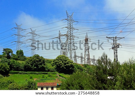High voltage electrical towers in a green field - stock photo