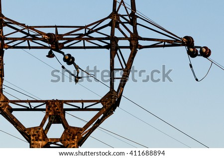 High voltage electrical transmission towers electricity pylons and power lines black silhouettes close up - stock photo