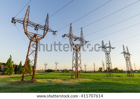 High voltage electrical transmission towers electricity pylons and power lines on green field - stock photo