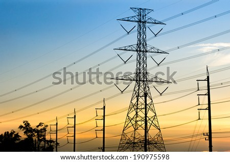 High-voltage electrical transmission towers with sunset background.