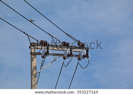 High voltage electricity pole with blue sky background.