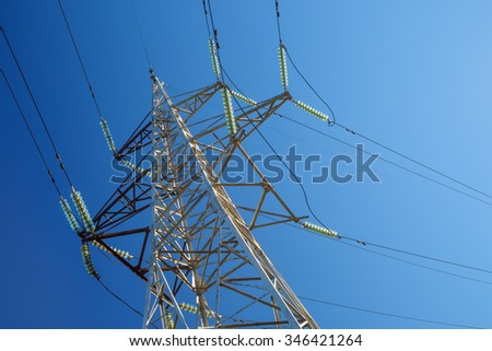High-voltage electricity pylon against blue sky. Electric power transmission. - stock photo