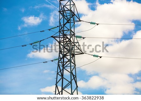 High-voltage electricity pylon against blue sky. Electric power transmission. High voltage wires. - stock photo