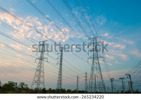 High voltage electricity pylon against the background sky of sunset light colors.