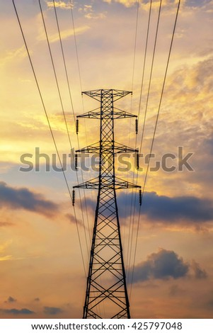 High voltage electricity pylon at time sunset - stock photo