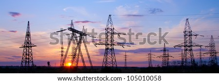 High voltage electricity pylon over sunset - stock photo