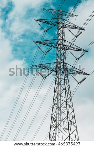 high voltage electricity pylon tower on cloudy blue sky