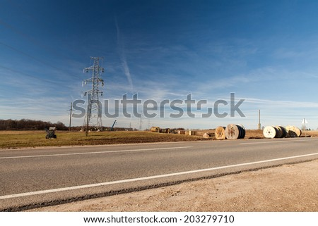 High voltage electricity pylon with workers on it building up a new power line on blue sky background with clouds - stock photo