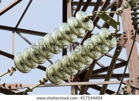 High-voltage insulator at high voltage power line pylon - stock photo