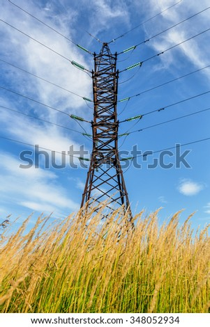 High voltage line among grass beneath cloudy sky - stock photo