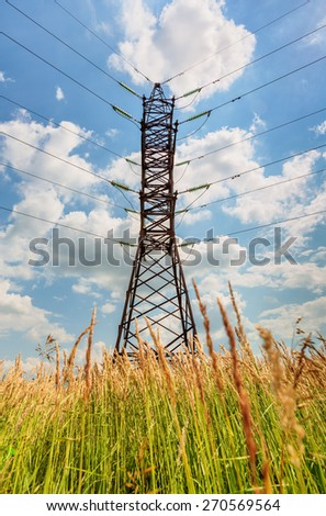 High voltage line beneath the blue cloudy sky - stock photo