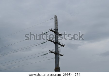 High voltage lines and power pylons in a flat and green agricultural landscape on a sunny day with cirrus clouds in the blue sky. - stock photo