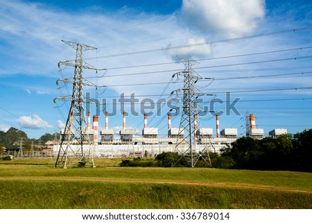 High voltage lines and power pylons in a flat and green agricultural landscape with cirrus clouds on blue sky, at Mae Moh coal-fired power plant, Lampang, Thailand. - stock photo