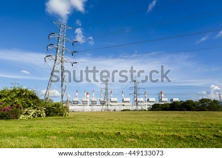 High voltage lines and power pylons in a flat and green agricultural landscape with cirrus clouds on blue sky, at Mae Moh coal-fired power plant, Lampang, Thailand.