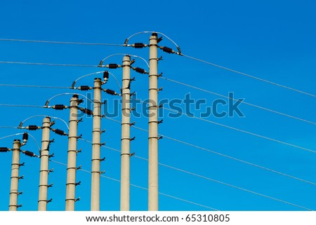 High-voltage pole against a blue sky - stock photo